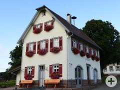 Begegnungsstätte Rathaus Gaugenwald mit blühenden Geranien an den Fenstern und zwei Sitzbänken vor dem Gebäude.
