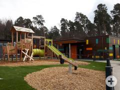 Blick auf das Kindergartengebäude. Im Vordergrund die Straße und eine Grünfläche mit Büschen.