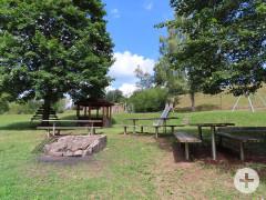 Grillstelle umgeben von Tischen und Sitzbänken auf dem Spielplatzgelände in Neuweiler.
