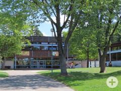 Blick zum Waldschulgebäude mit wenigen Schülern im Schulhofbereich. Im Vordergrund die Zufahrt und Grünfläche mit großen schattenwerfenden Laubbäumen.
