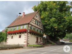 Schönes Fachwerkhaus mit grünen Fensterläden und blühenden Geranien unter den Fenstern, die wie ein breites rotes Band die Hauswände verzieren. Rechts ragt ein sehr großer Laubbaum über das Heimatmuseum hinaus.