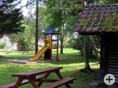 Blockhütte und Tisch mit Bänken an der Grillstelle auf einer Waldlichtung. Daneben ein Spielplatz mit Rutschbahn und weiteren Spielgeräten.
