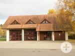 Das Feuerwehrgerätehaus hat drei kleine Dachgauben und zwei verglaste Tore. Daneben ist der Eingangsbereich und eine Garage.