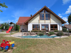 Kindergartengebäude bei tiefblauem Himmel. Links eine rote Rutschbahn, vor dem Gebäude der Sandkasten und Wiese, auf der ein buntes Holzauto auf einer Wackelspirale steht.