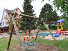 Im Vordergrund ein Holzgestell mit zwei Kettenschaukeln. Dahinter der Sandkasten und rechts davon eine bunte Rutschbahn. Im Hintergrund teils verdeckt von hohen Bäumen das Kindergartengebäude.
