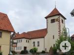 Am Kirchengebäude ist links ein Vorbau für den Eingang, rechts der Glockenturm. Am Treppenaufgang seitlich Büsche. Vor der Kirche steht ein Steindenkmal für gefallene Soldaten.