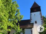 Blick nach oben zum Kirchturm bei tiefblauem Himmel. Ein großer Laubbaum links verdeckt einen Teil des Kirchegebäudes.