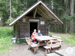 Auf einer Waldlichtung steht eine Blockhütte, davor ein Tisch mit Bänken rundum. Zwei Wanderer sitzen am Tisch und ruhen sich aus.