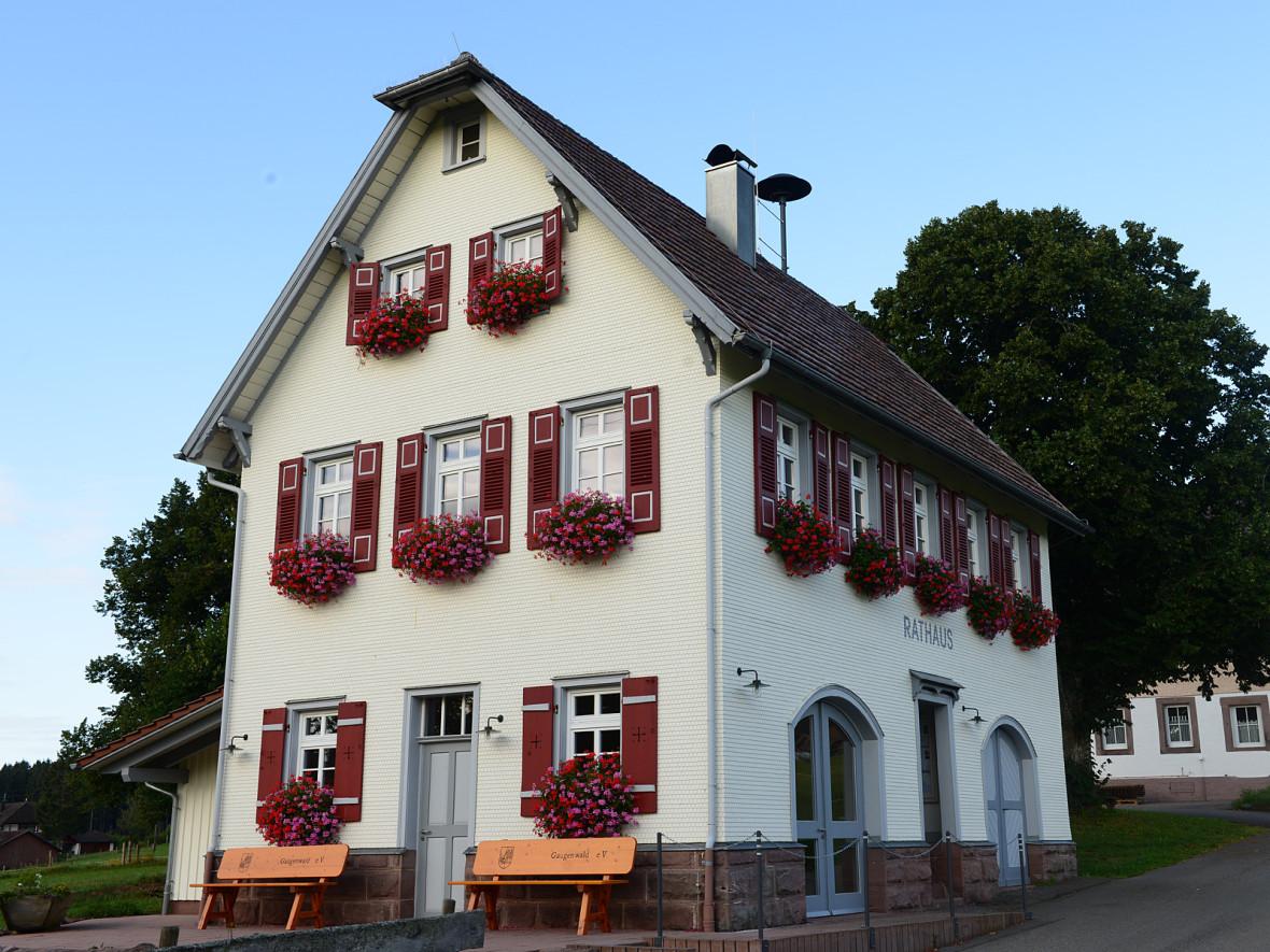 Links das Rathaus Gaugenwald, in der Mitte die Kirche, die teilweise von einer großen Linde verdeckt wird, und rechts das ehemalige Schulhaus. Im Vordergrund des gesamten Bildes eine grüne Wiese.