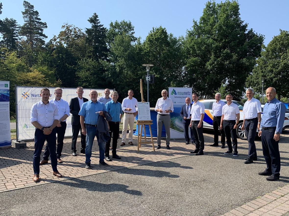 14 Personen stehen auf dem Dorfplatz in Bad Liebenzell-Monakam. In der Mitte sieht man eine Tafel mit den Unterschriften der Vertragspartner, im Hintergrund sieht man die Firmentafeln des Landkreises, der Netze-BW und des nsw-Netz