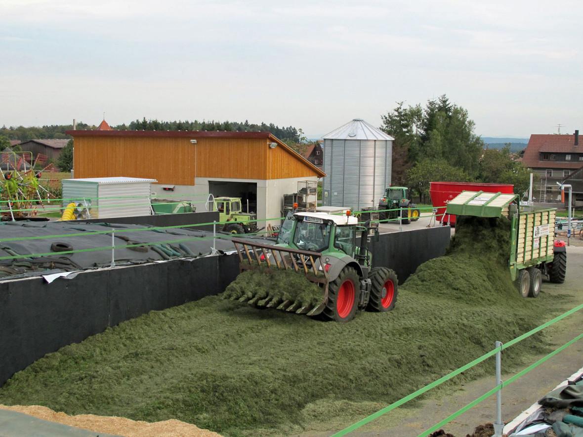 Bei der Biogasanlage wird Grünschnitt angeliefert und von einem landwirtschaftlichen Anhänger abgeladen. Ein Traktor verteilt die Biomasse auf eine Fläche.